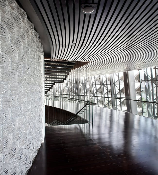 The glass brick wall in the main auditorium lake side lobby is made of 20.000 glass bricks with a wave pattern relating to the surrounding lake and to the curved bamboo block wall inside the auditorium. (Photo: Kari Palsila)