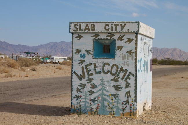 A welcome-sign at the entrance to Slab City. Credit: Wikipedia