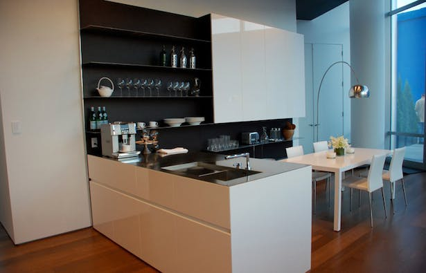 """Doors: White Glossy lacquer, 22 mm (3/4"""") thick with 30° top edge Sliding Counter: Thermo Oak with electronic movement (counter thickness 8cm = 3 1/8"""") Counters: Hand crafted brushed stainless steel, 3 mm (1/8"""") thick with soldered sinks and retractable faucet Hood: Custom by Minimal Open Shelving: Thin stainless steel shelving system 6mm (1/4"""") thick with Thermo oak back panels"""