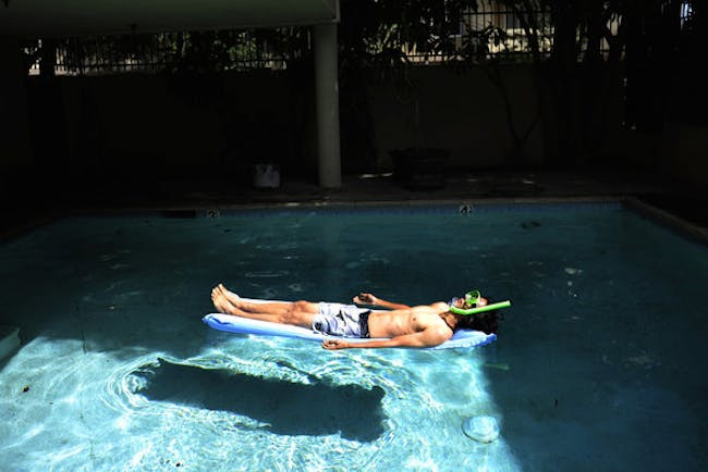 Joseph Lee, 23, a UCLA graduate from Vallejo, teamed up with research partner Benedikt Gross to produce 'The Big Atlas of L.A. Pools.' Here he lounges in one of the blue oases. Susannah Kay / Los Angeles Times.