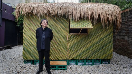 Shigeru Ban posing with a replica of one of his shelters made from green bamboo to address the earthquake in Ecuador. Photo: Brook Mitchell​