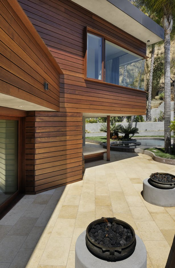 The intimate outdoor living room sits to the West-side of the home and includes a built-in sofa, twin fire pits and white travertine pavers. It leads to the outdoor dining room, the home's primary dining area.
