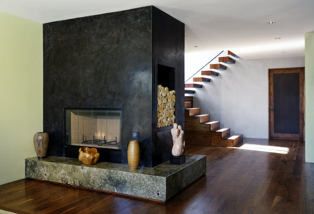 The focal point of the living room is the large, smooth Venetian plaster fireplace and granite hearth. Directly behind it is the front door and the glass 'jewel box,' which floods both floors of the house with light. The door at right leads to the garage.