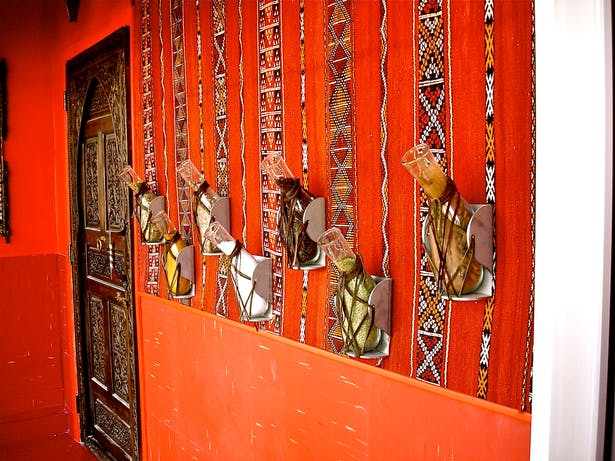 Restaurant vestibule with traditional 'cliches' such as Berber wall hanging, lanterns [not shown], heavily carved door and spice containers [which are actually modified army surplus urine bed pans]