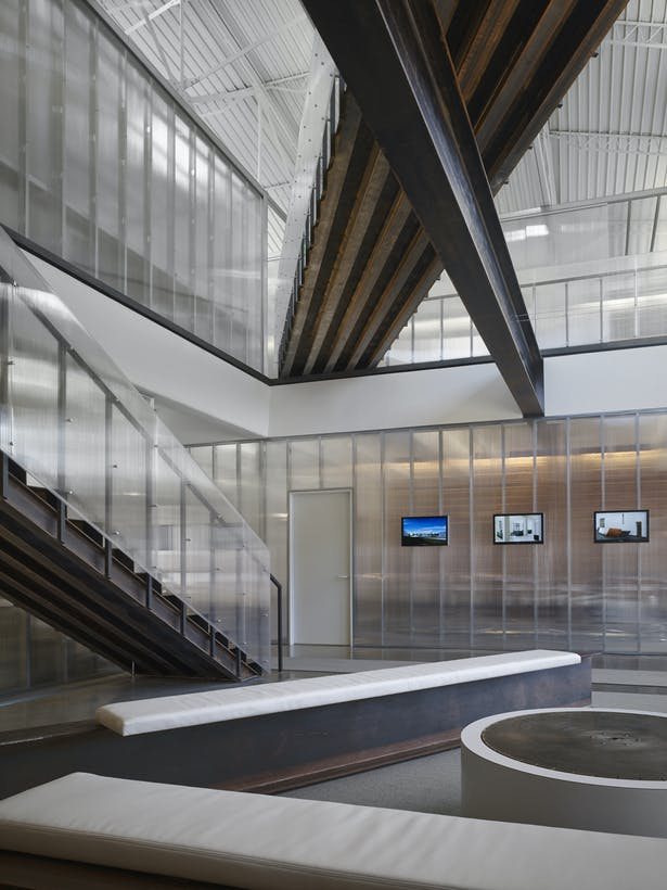 Main lobby view looking east. Historic steel beam is exposed and supports a new steel stair and bridge. The clear polycarbonate walls expose all of the internal construction. A clear illustration of the x-ray concept.