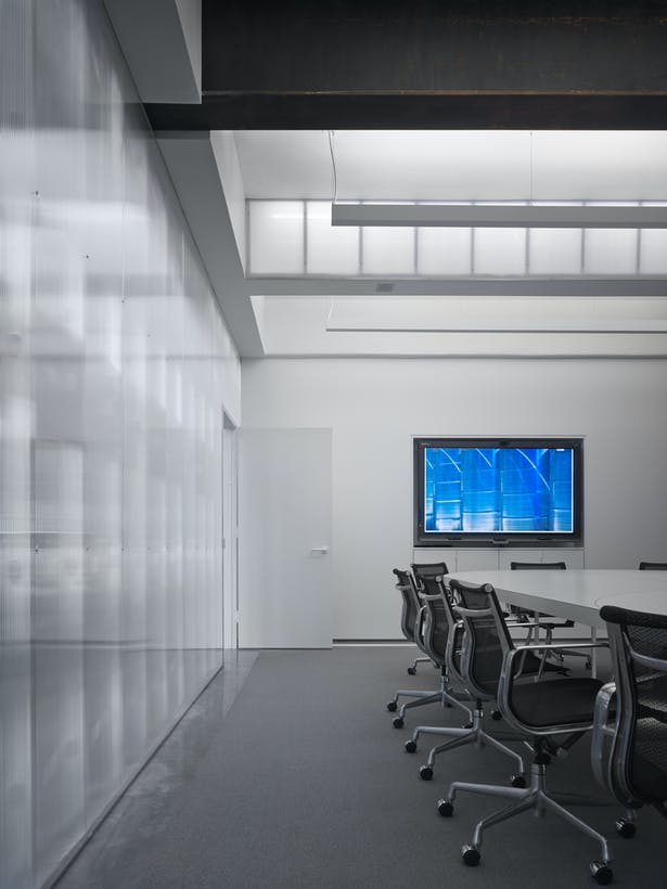 Ground level conference room looking north. Conference table has lighting underneath. The new polycarbonate beam / light is exposed as well as the indirect room lighting. Clear polycarbonate separates the entry gallery from the conference room.