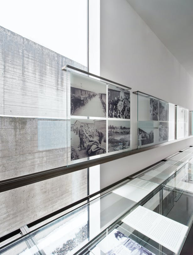 The view of the surrounding wall of the memorial is overlaid with exhibition objects showing the killing and extermination of inmates.