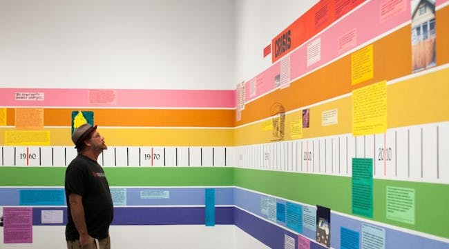 A rainbow-colored timeline of 20th-century American housing on the walls wraps around the exhibit, each strand of the rainbow explaining the different factors leading up to the current state of the U.S. housing industry. Photo by Marianne Williams.
