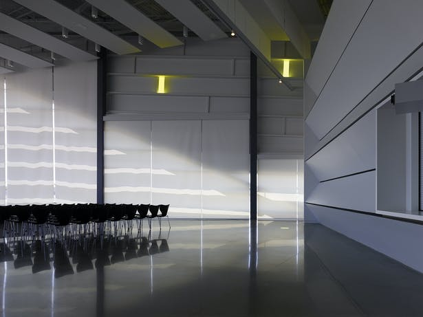 "The Performance Hall looking towards the ""nose"" of the building. Shade slits create pencil thin light leaks that form and reflect the interior space."