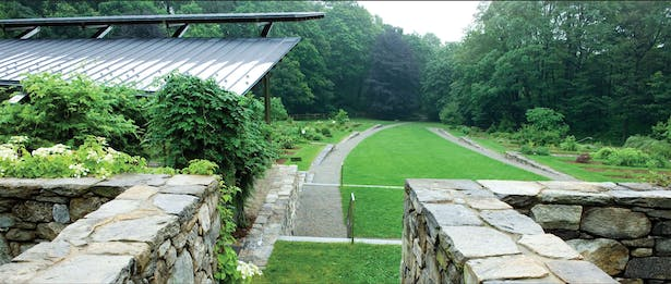 The soft arc of the curving path rises alongside stone walls which grow from slope, forming level shrub planting beds. The Event Pavilion sits atop the slope and commands an expansive view of the entire garden. photo Andrea Jones