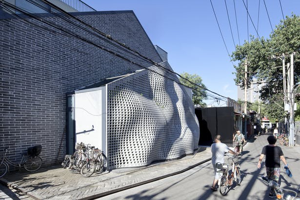 The façade enters the space of the hutong as a flowing fabric