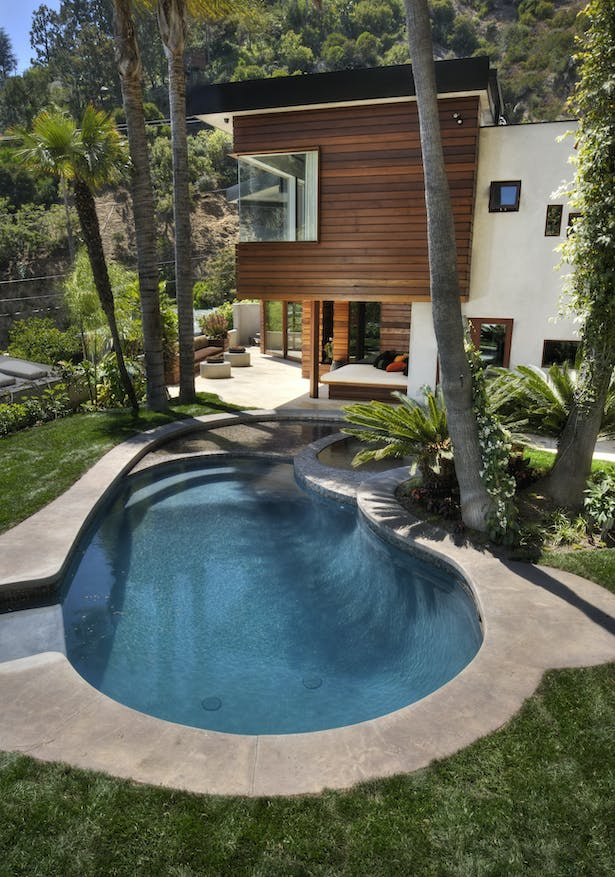 """Now shallower, the existing kidney shaped pool was redesigned to incorporate a jacuzzi and a 3"""" deep wading pool for """"floating"""" lounge furniture."""