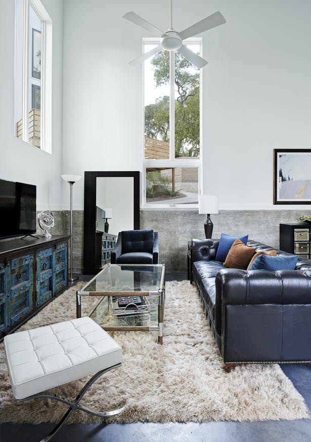 The owner's eclectic sensibilities balance with the crisp and economical material selections. Tall, pre-manufactured windows are arranged in vertical bands to accentuate the height of the space and capture framed views. White-framed walls sit atop an exposed concrete retaining wall that submerges the house waist-deep into the site in this shot.