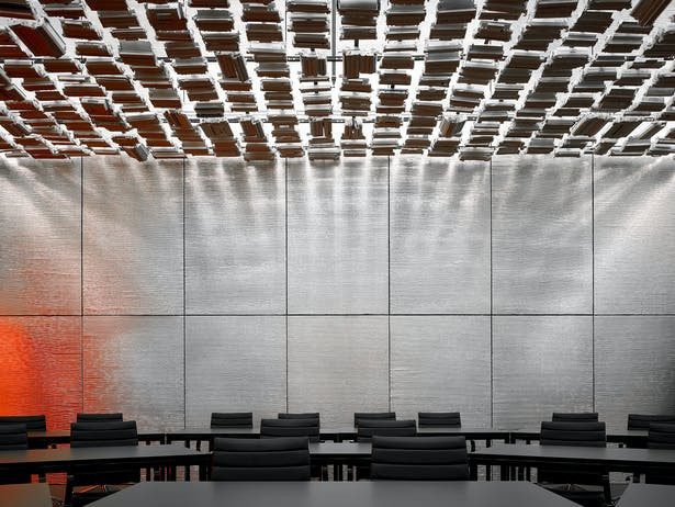 """The presenter's view of the training room inspires the guests. Suspended recycled toner cartridges create a celestial ceiling. The reflection to the left has been affectionately described as the """"smudge."""""""