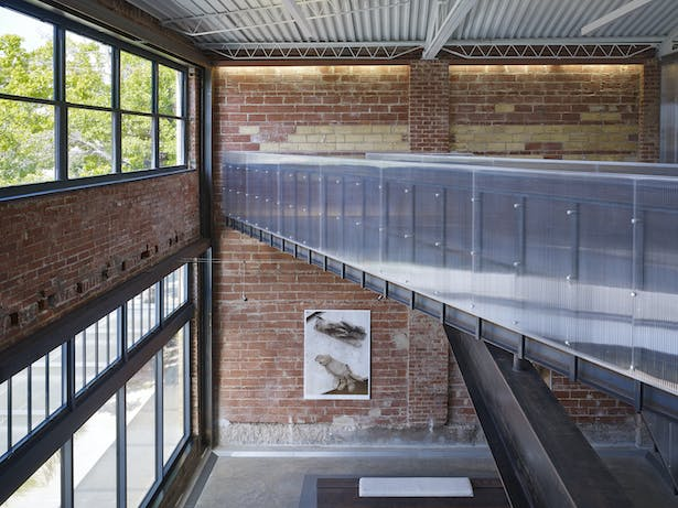 The entry lobby overlook showing historic beam pockets on the left, the 1930s bowstring truss roof, and the new steel and polycarbonate bridge.