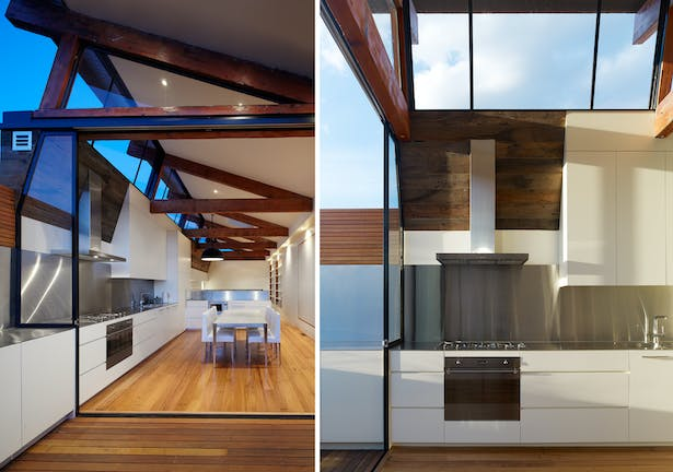 The top living level is completely open plan, with spaces defined by the reclaimed roof trusses - simply raised up from the original roof. Light floods in the living level, via clerestory glazing between the reclaimed trusses. The Kitchen & Dining area connects effortlessly to the rooftop terrace. Photo: Peter Bennets