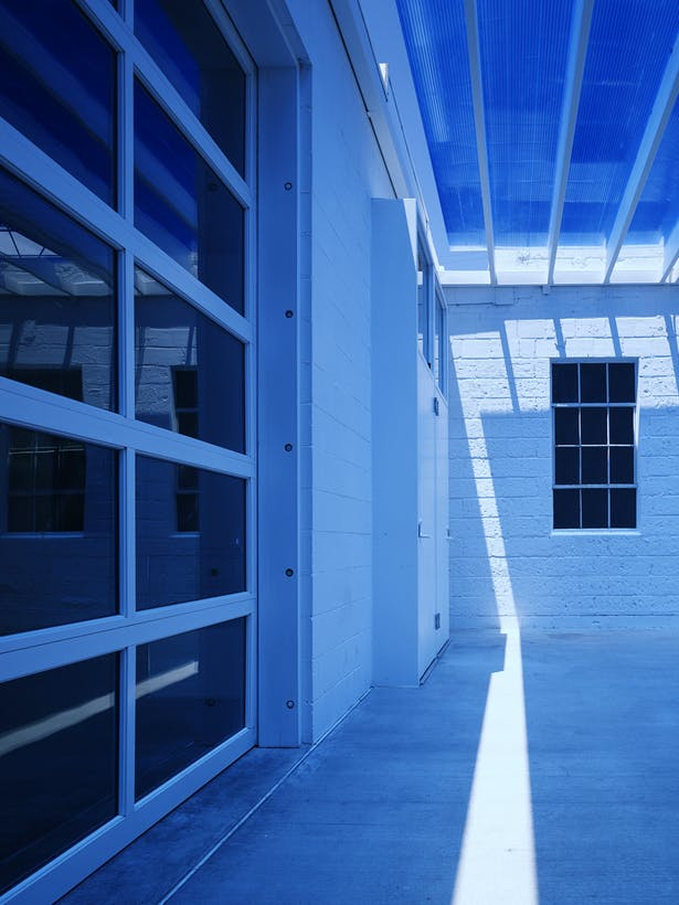 Detail under the entry canopy showing the blue polycarbonate and the existing steel windows. The sun creates magical changes throughout the day. The space remains a deep blue during daylight hours.