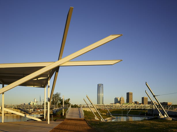 A triangular sun shade balances on carefully nested steel beams.