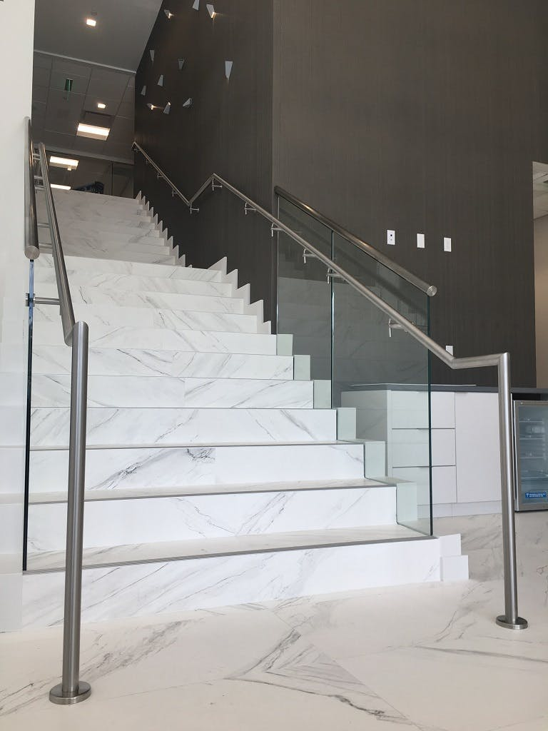 Rounded Stainless Steel Handrails in a Brushed Finish were installed on both sides of this Commercial Staircase, as per Florida Building Code.