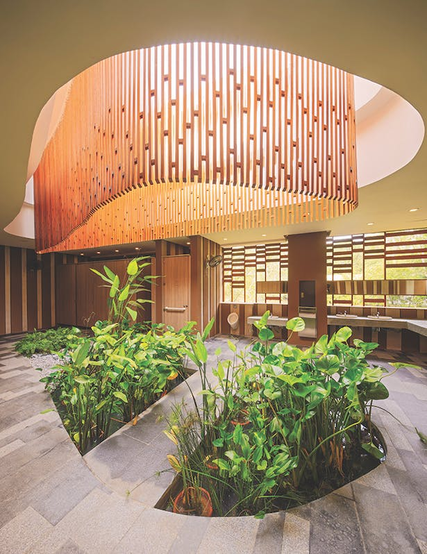 The central skylight with a wooden trellis veil enlivens the interior of the bathrooms in the entrance plaza zone, while preventing rainwater from splashing into the space