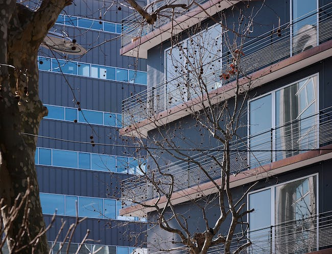 Details: 'Large glazed openings, with exterior carpentry work in aluminum on the street façade and in wood and aluminum on the courtyard façade, create a linear purity.' (Photo: Julien Lanoo)