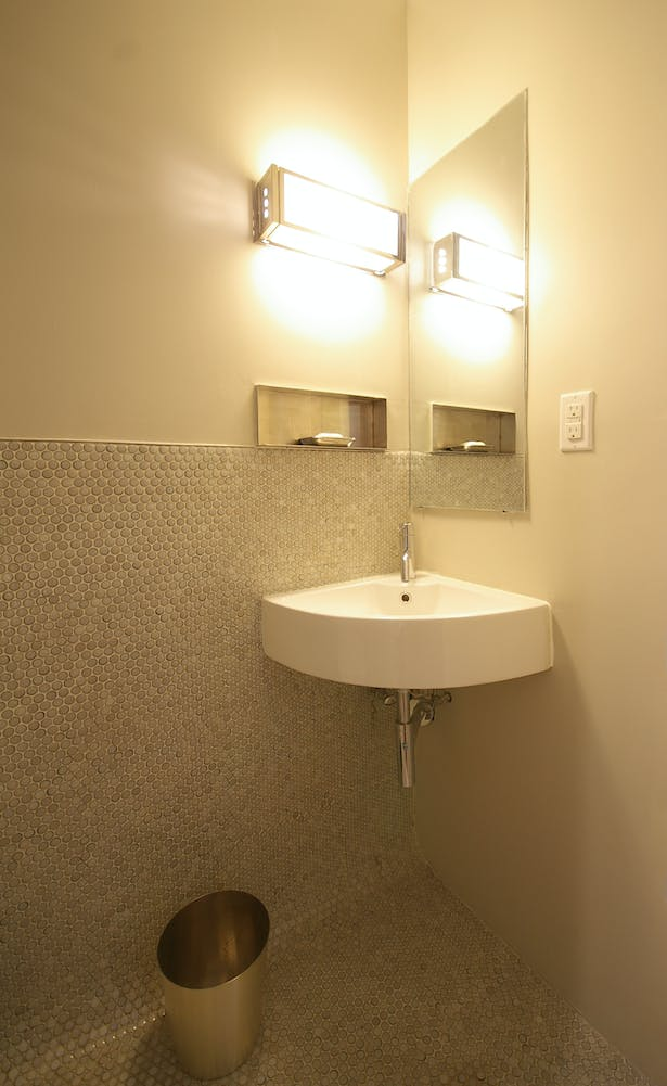 Small powder room exploits the tiny scale of penny tiles at floor and wainscott