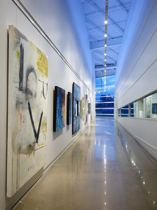 The art gallery and boat storage spaces are placed side by side to illustrate their connection. Track lighting and blue atmospheric lighting create universal space.