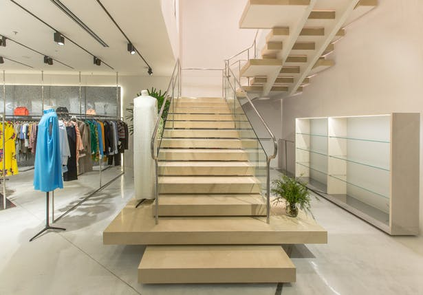 The climax is represented by the monumental staircase of beige Hauteville stone from Southern France: huge stone slab as steps expand the sales floor area, accompanying clients onto the second floor of the store on a journey through a unique luxury shopping experience.