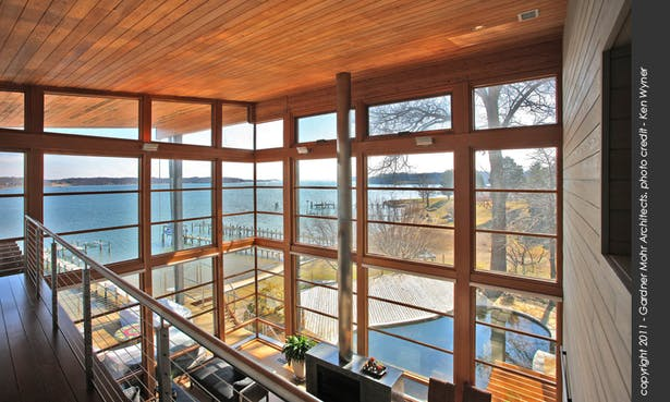 View from the upper level bedrooms, overlooking the living room and its fabulous water vista.