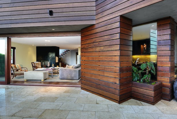 At the rear of the house, the indoor and outdoor spaces flow into one another through custom retractable doors and full-height glass walls. The exterior is clad in red mangaris from Indonesian forests managed by sustainable practices. Limestone pavers cover the patio floor.