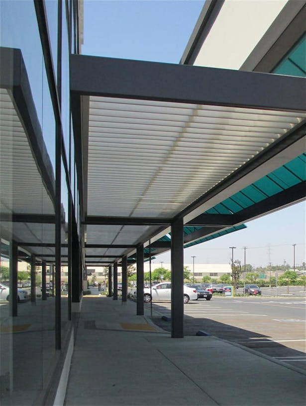 A louvered trellis structure now accompanies the converted office 'glass box' with shop spaces / the structure also incorporates a large sign board for multiple tenants and canvas awnings to enliven the shopping activity / it is not connected to the existing building due to potential seismic impacts / its entirety is supported by a single grid line of tube steel columns