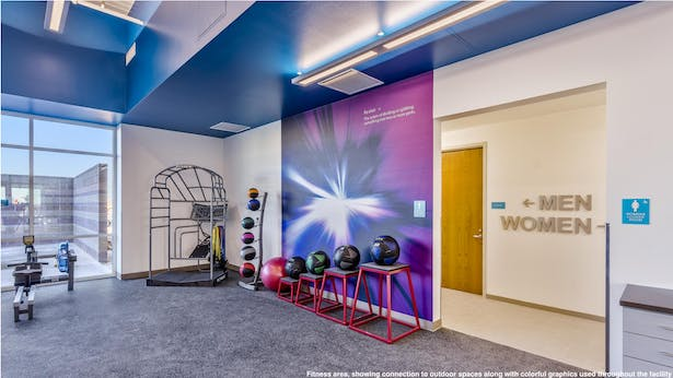 Fitness area, showing connection to outdoor spaces along with colorful graphics used throughout the facility.