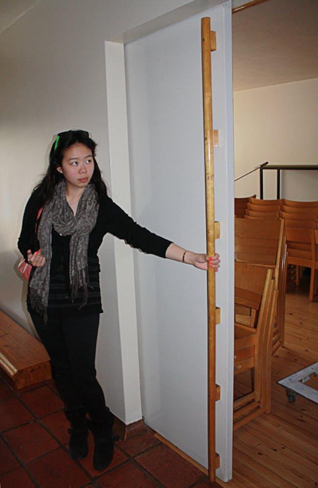 Jennifer Wong displaying the scale of the door detail at the Vuoksenniska Church (Church of 3 Crosses), Vuoksenniska, Finland 1958