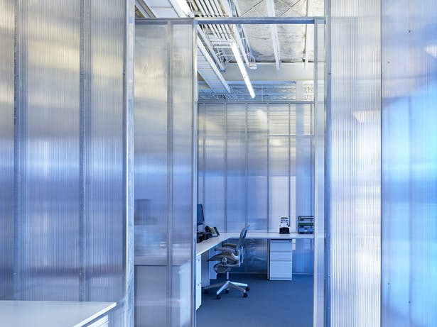 A typical open office space created by clear polycarbonate panels. The perimeter blue panels provide a softened blue hue.