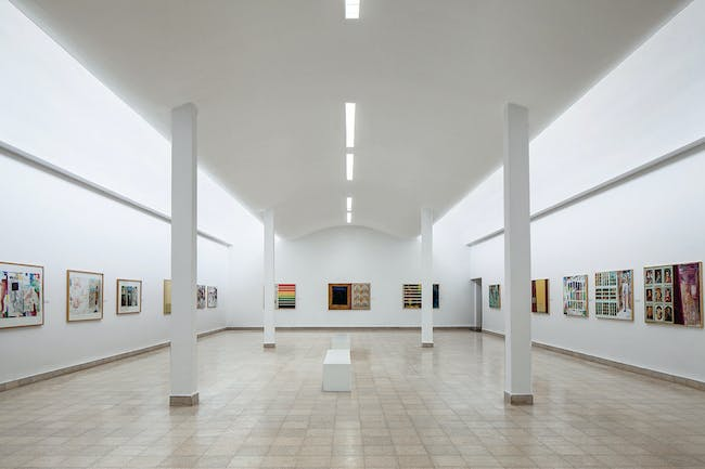 A simple gallery with slender columns and an invisible light source - photo by Amit Geron