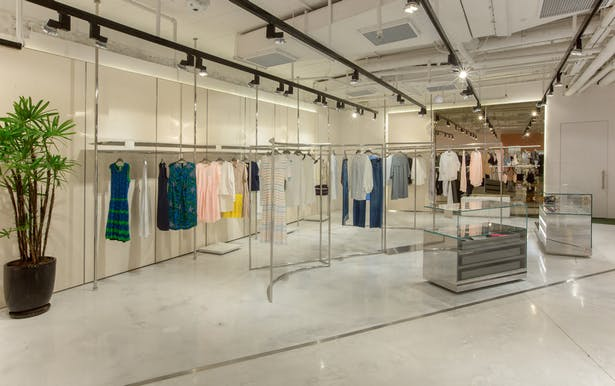 Inside, large glass displays composed of mirrored surfaces of polished steel and lacquers in pastel shades enhance the fashion collections, making the garments visible and appealing