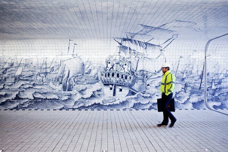 A pedestrian walks next to a detailed tableau inpired by the work of Cornelis Boumeester and designed by Irma Boom Office