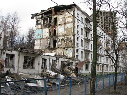 "A half-demolished ""Khrushchyovka"" apartment block in Moscow with new development behind. Image: Wikipedia."