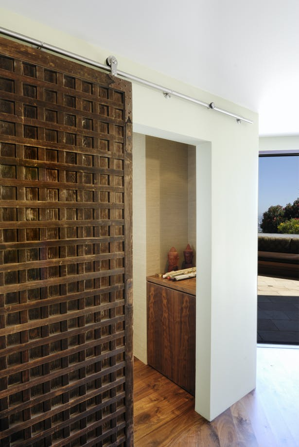 Off the living room, a 300-year-old monastery door Cummins bought in Southeast Asia slides open to reveal his home office. The door is mounted on clean-lined, stainless-steel track by Barn Door Hardware.