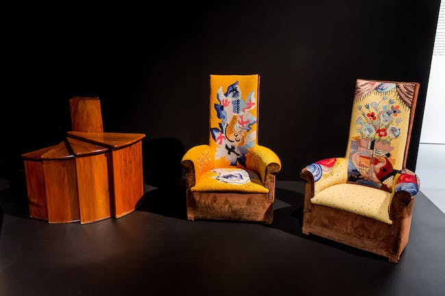 Left to right: Pierre Chareau, telephone fan table, c. 1924, wood. Private collection, New York; Pierre Chareau, Two high-backed chauffeuses (fireside armchairs), c. 1925, wood and velours, with tapestry upholstery by Jean Lurçat, reupholstered 1968. Private collection. Photo: Will Ragozzino/SocialShutterbug.com. Exhibition design by Diller Scofidio + Renfro.