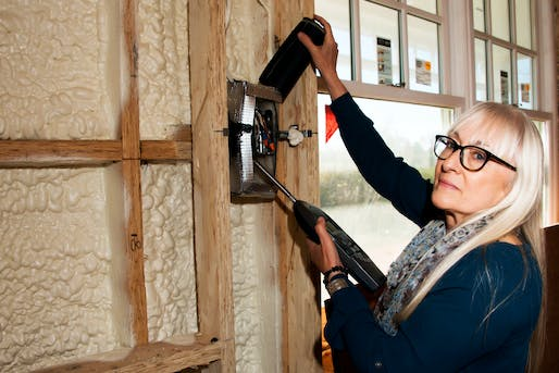 Bonnie Schnitta, an acoustical consultant, measures how much sound is coming through a wall outlet - Credit Daniel Gonzalez for The New York Times